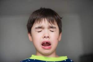 Crying boy with lost tooth