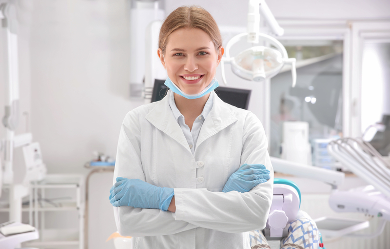 Young female periodontist standing in dental office.