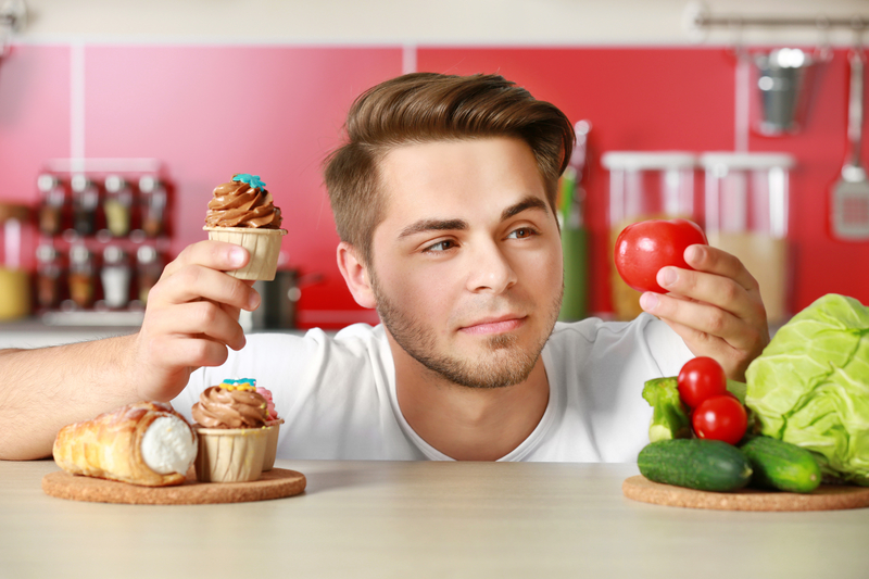 man holding a cupcake in one hand and a tomato in the other with a questionable look on his face.